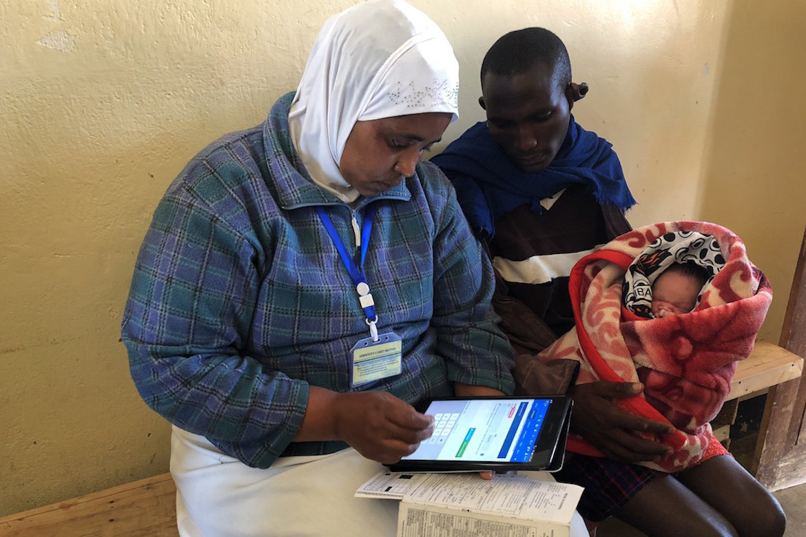 A female health worker records immunisation data for a father and his child