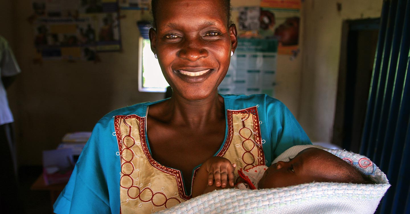 GAVI/2014/Mike Pflanz/South Sudan - A woman smiles into the camera holding her baby during the pentavalent vaccine introduction in South Sudan