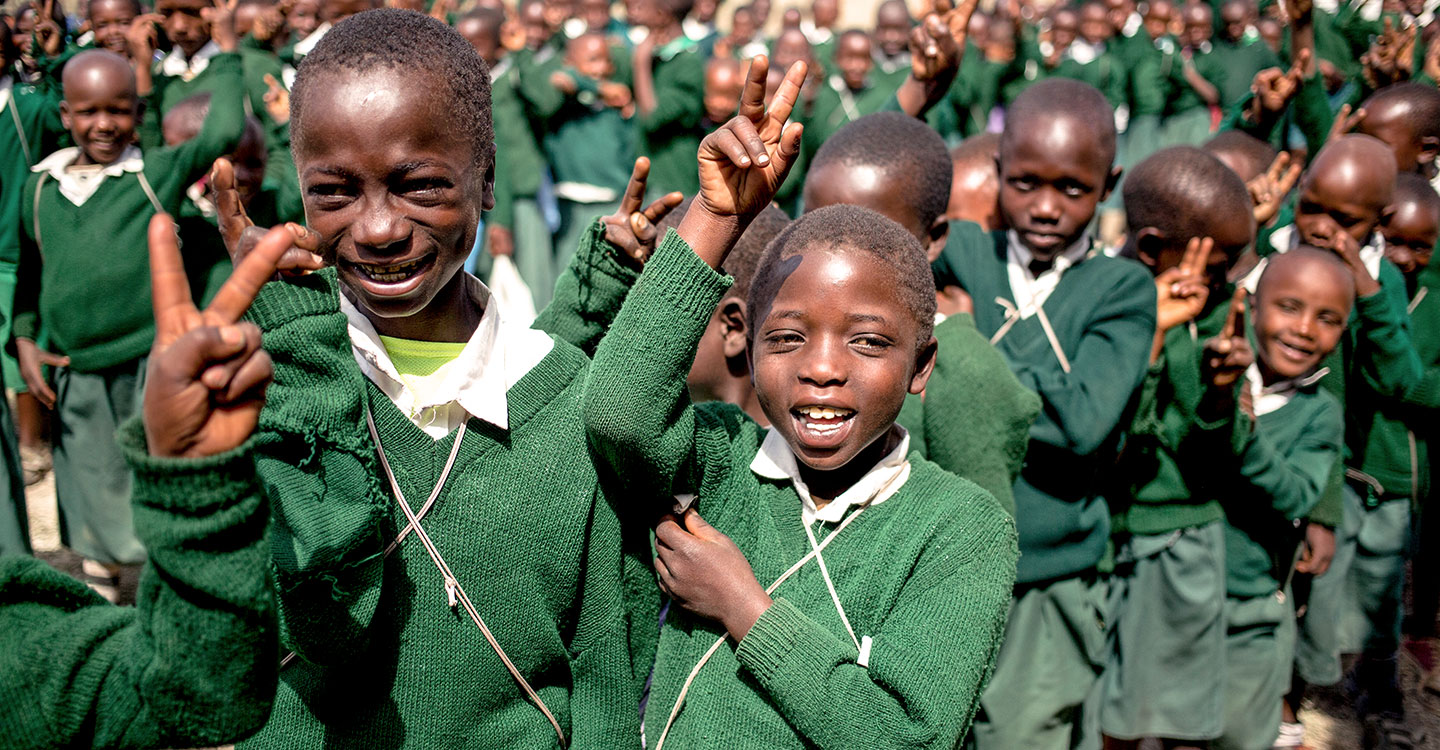 children holding up peace signs and smiling