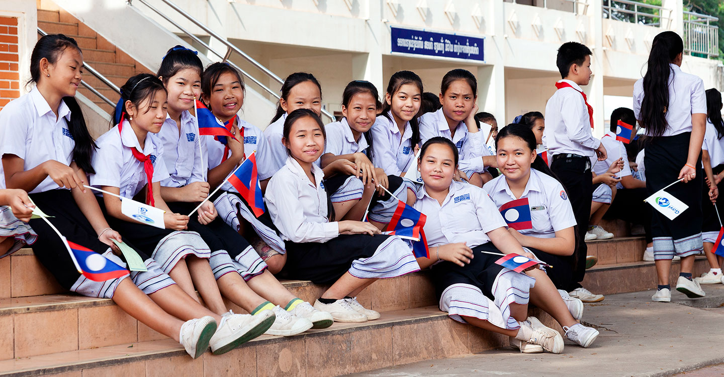 School girls smile for a picture while holding the Laotian flag with the Gavi logo on the back
