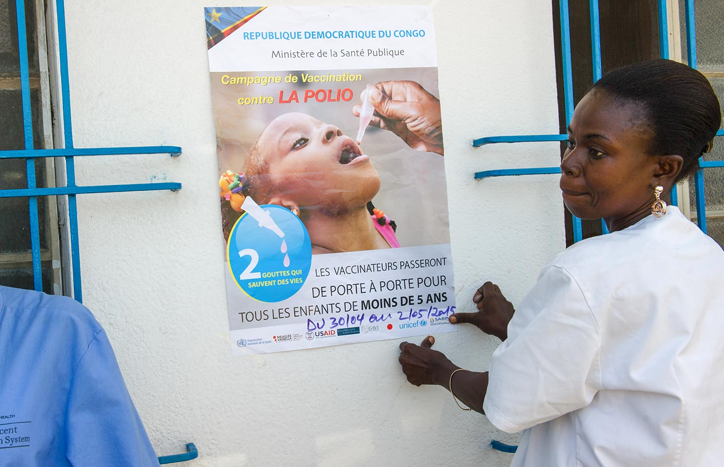 GAVI/2015/Phil Moore- A nurse attaches a poster advertising a door-to-door polio vaccination campaign in Kinshasa, Democratic Republic of the Congo, on April 27, 2015
