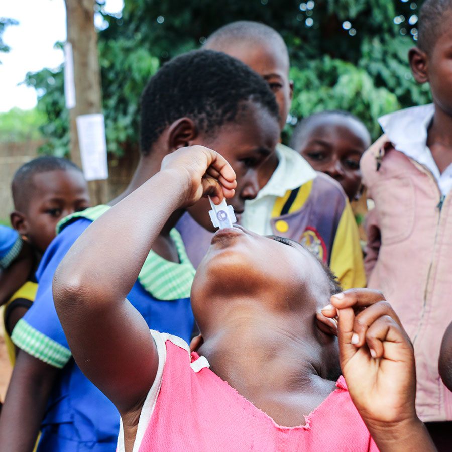 Little girl administering oral cholera vaccine to herself in Malawi
