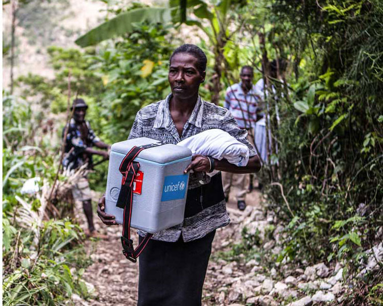 health worker helps carry cold chain equipment in Haiti. Credit: Gavi/2013/Evelyn Hockstein
