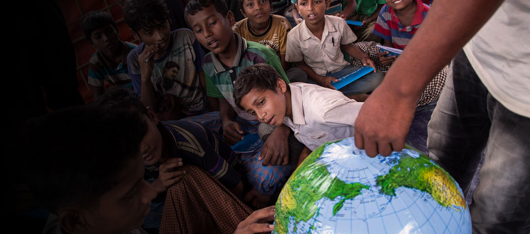 © UNICEF/UN0141027/LeMoyne/Bangladesh- Students look at an inflatable globe, part of the educational supplies contained in a School-in-a-Box, at a new Transitional Learning Centre in the Uchiprang refugee camp, near Cox's Bazar, Bangladesh