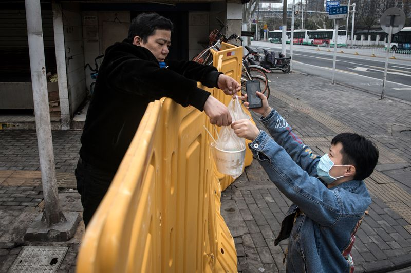 Image from Nature article – A man wearing a mask sells breakfast to nurses behind a makeshift barricade wall in Wuhan, China. Social distancing has been used to halt the transmission of the coronavirus in China. Credit: Getty