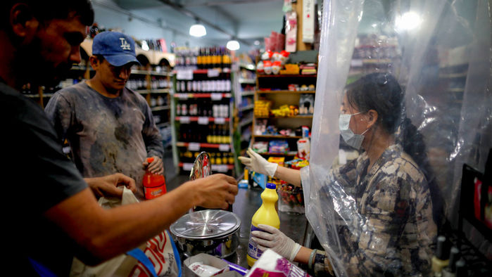 Iamge from sciencemag article: A supermarket cashier in Buenos Aires, Argentina, waits for costumers behind a makeshift plastic curtain as a precaution against the spread of the coronavirus that causes COVID-19.