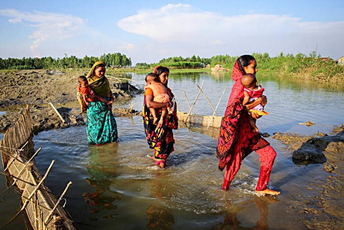 "Women in Char Doglas Island, Sirajganj, Bangladesh, carry their children to get vaccinated. Most inhabitants of ""chars"", the remote floodplain sediment islands that dot the Ganges delta, live a hand to mouth existence. Women often give birth at home and lack extensive formal education. However, thanks to successful vaccination campaigns these mothers are aware of the importance of immunisation and often travel long distances to get their children to the nearest vaccination center."