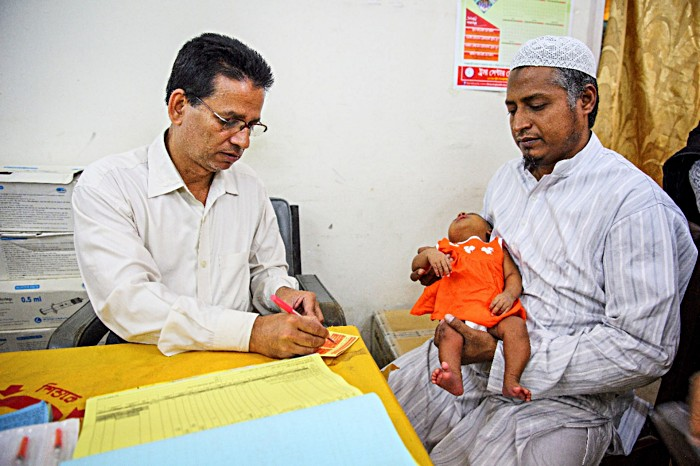 Kaosar Alam watches as a healthcare worker fills out his daughter Radia's vaccine registration card in Dhaka, Bangladesh. While this means Radia can receive additional recommended vaccines in the future, many children – 20 million around the world – do not receive a basic course of vaccines, due largely to a lack of registration at birth. Gavi and partners will be piloting a project in Bangladesh in early 2020 to try to address this issue by creating digital identities for children under 5. If successful, t