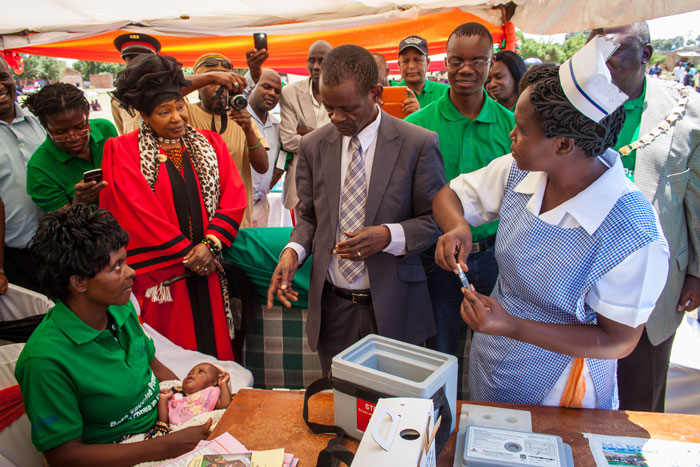 Honourable Dr Joseph Katema, Minister of Community Development, Mother and Child Health, speaks with Lisa Chinyama, the mother of the first child to be vaccinated during the ceremony, as a community health worker prepares the vaccines.