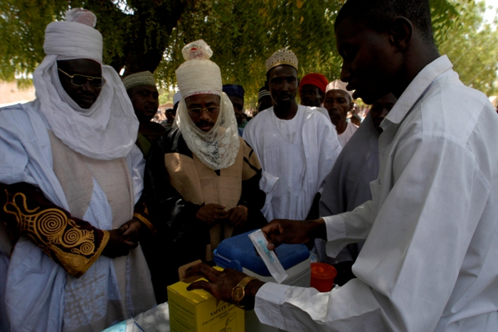 At an Immunisation Day Plus held at the fixed immunisation post in Isawa village, Muhammed Sabo Abdulkadir, the district head of Giade (right) and Yaya Abubakar, the village head of Isawa (left), are seen by members of the community to be endorsing vaccination.