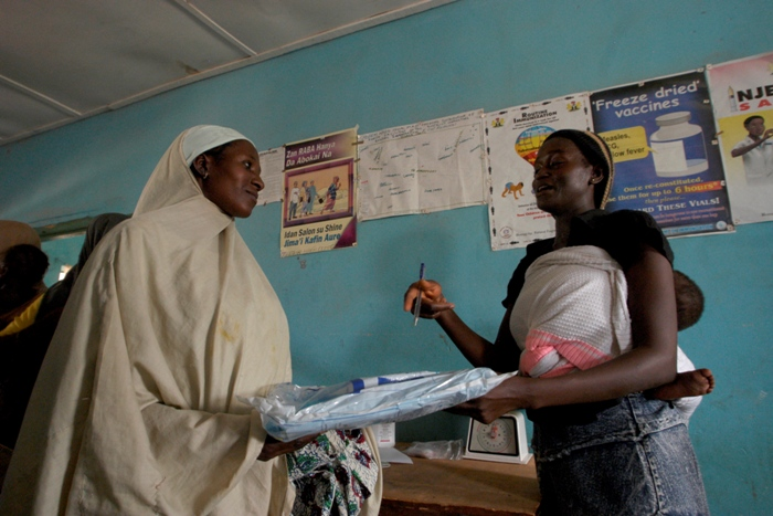 As a reward for fully immunising her child, each mother receives a treated bednet to protect her family against malaria, once she has completed her yellow vaccination card.