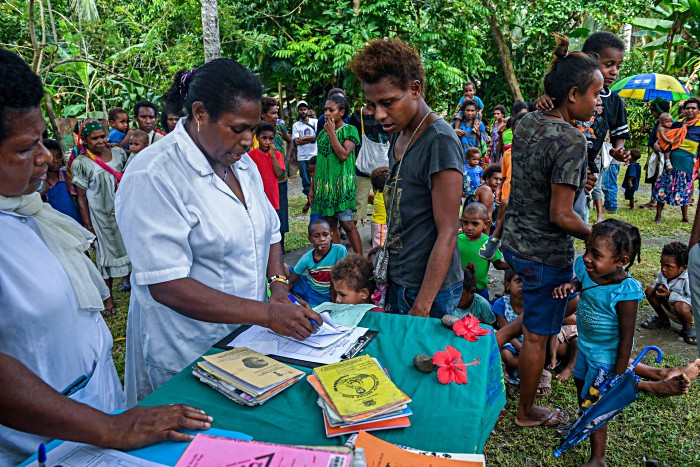 Officer-in-charge Daisy Basa (centre) checks a child's vaccination card at the Malahang Health Clinic. More than 2900 health workers, vaccinators and volunteers have been mobilised to vaccinate almost 300,000 children under five years old in Morobe, Madang and Eastern Highlands provinces.