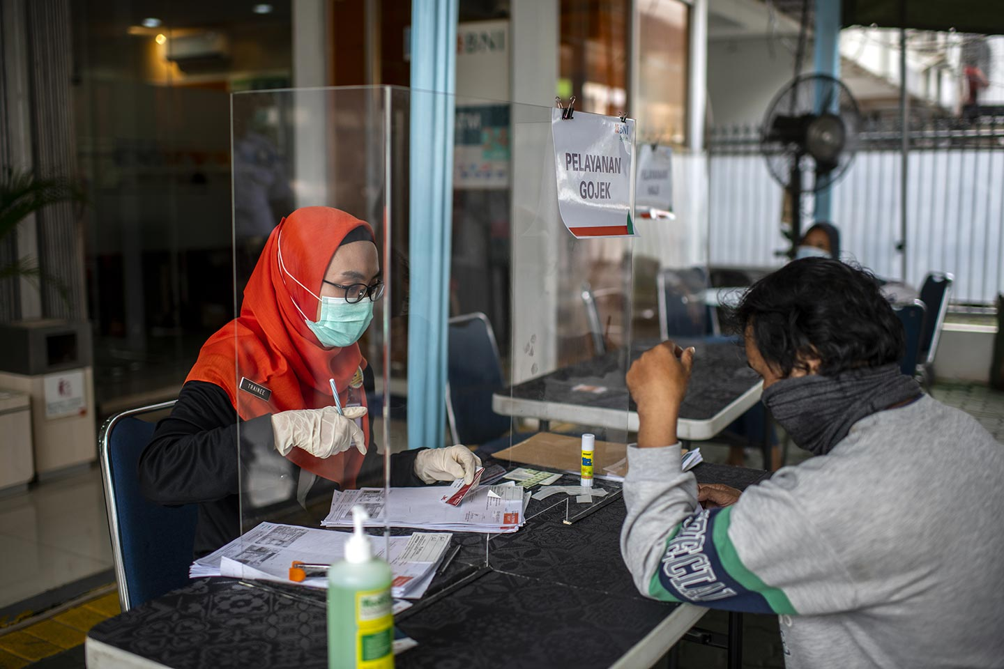 Bank officer (left) serving to customer in front of the bank using protective glass during Covid-19 outbreak in South Jakarta, Indonesia on 31 March, 2020. Almost all bank in Jakarta implement a social distancing for customer services. Credit: UNICEF/2020/Arimacs Wilander