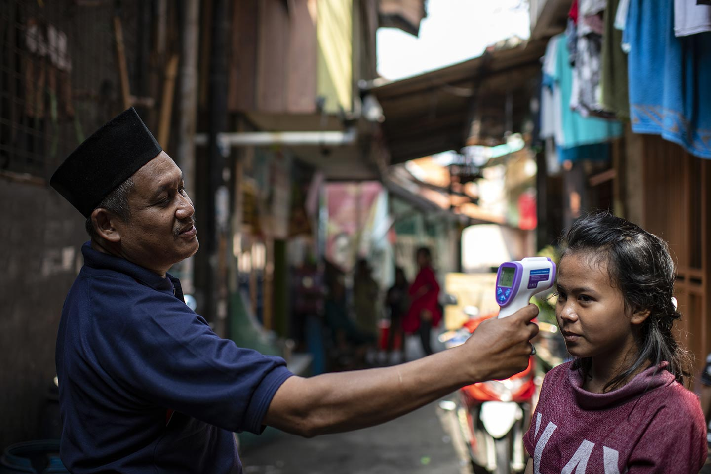 Sudirman, 55, head of RT (left) is checking Zahra temperature during the Covid-19 outbreak in slum area in West Jakarta, Indonesia on 1 April, 2020. Credit: UNICEF/2020/Arimacs Wilander