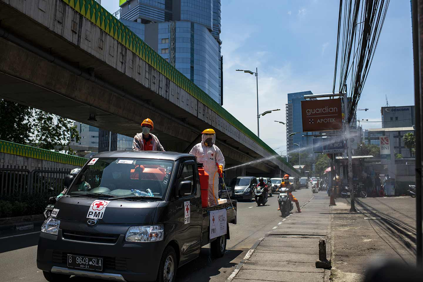 The Indonesian Red Cross spraying disinfectants on its own streets to fight with Covid-19 in Jakarta, Indonesia in March, 2020.  Credit: UNICEF/2020/Arimacs Wilander