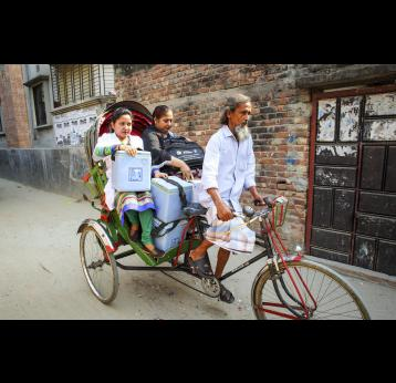 Man on tricycle with health workers sitting in the back with vaccines in cool boxes
