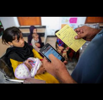 GAVI/2017/Asad Zaidi-An EPI worker, Mohammad Saim, entering Adeel's (15 days old) data into the EVACC mobile app during an urban slum field visit in Bund Road Lahore, Punjab province