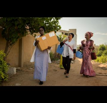 "Gavi/2018/Simon Davis- Health workers from the Dakar North District immunisation ""outreach"" team set out on foot after reaching the end of the built road. They are taking vaccines to families in Nabisouikr, one of Dakar's slum areas"