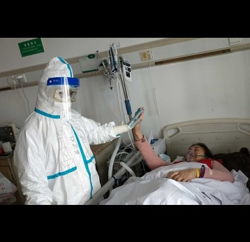 Nurse and patient high five in hospital room - credit: WHO/2020