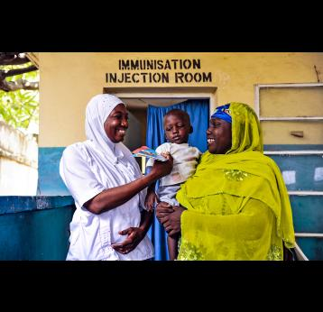 Two health workers holding a baby in front of Immunisation injection room- GAVI/2013/Adrian Brooks