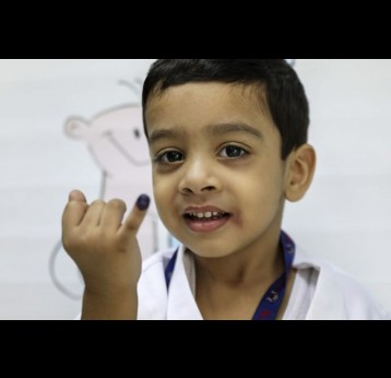 A boy proudly shows the ink mark on the tip of his finger. He was vaccinated against typhoid during the campaign in Sindh province in November 2019. PATH/Asad Zaidi