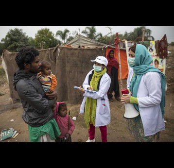 Sadaf Fareed, with her team talking to the man about the vaccination of his children.  Credit: Gavi/2020/Asad Zaidi