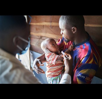 A father holding his son while he finally gets vaccinated – Gavi/2021/Christophe Da Silva