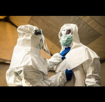 Medical staff check each others protective suits. Photo by SUMY SADURNI/AFP via Getty Images