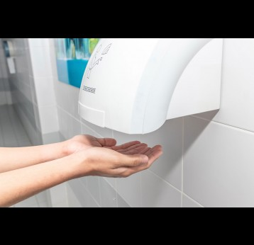 Automatic hand dryer in public toilet or restroom