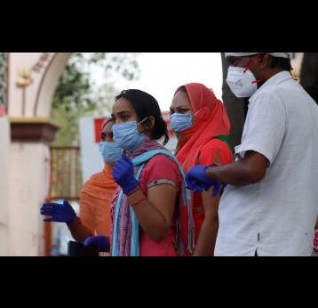 Indian health workers wearing personal protective equipment (PPE) and relatives carrying the mortal remains of a COVID-19 victim at the cremation ground