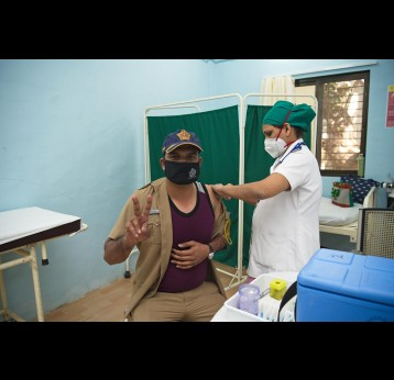A police personnel receives COVID-19 vaccine.