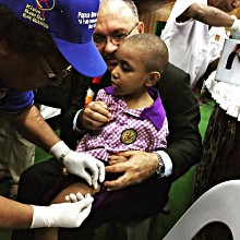 PNG's PM Peter O'Neil and a child getting vaccinated at today's polio and measles-rubella launch