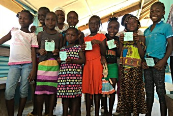 A group of girls show their vaccination cards during a HPV vaccination session in Liberia