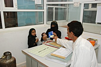 A mother receives a vaccination card for her children at a health centre in Yemen