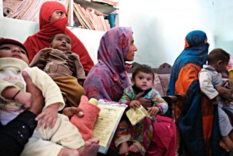 Mothers waiting to get their children immunised at a vaccination site in an area of Lahore
