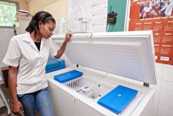 A health worker looking inside a vaccine refrigerator, monitored using the Nexleaf Analytics ColdTrace wireless remote temperature technology.