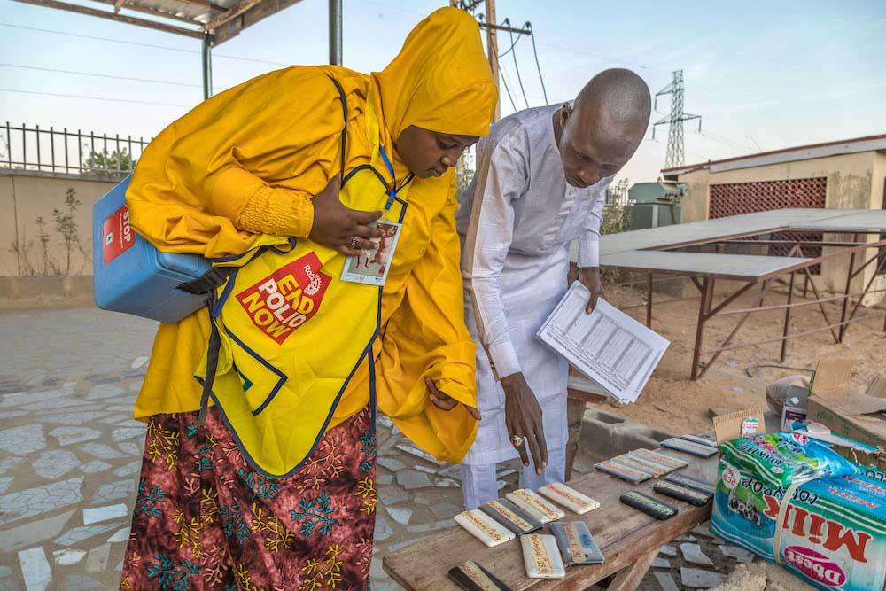 A vaccinator in Maiduguri collects materials for a door-to-door polio vaccination campaign, including vaccine box, recording sheet, mobile phone and marking pen. © Andrew Esiebo/WHO
