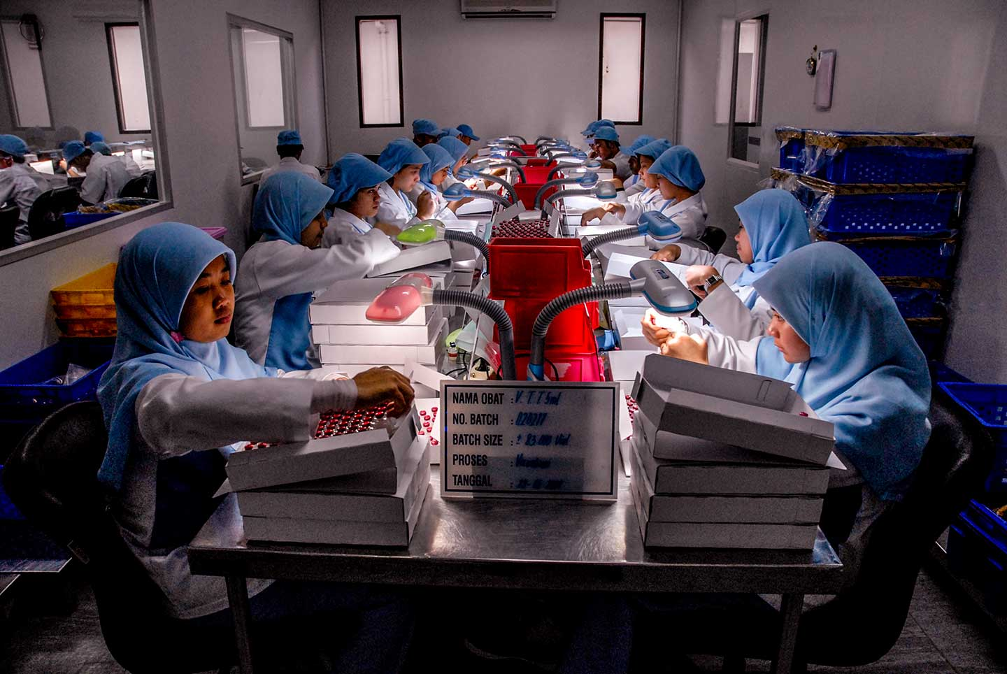 Workers look at the filling process of HepB vaccine filled in Uniject syringes at the Bio Farma serum factory. Credit: Edy Purnomo