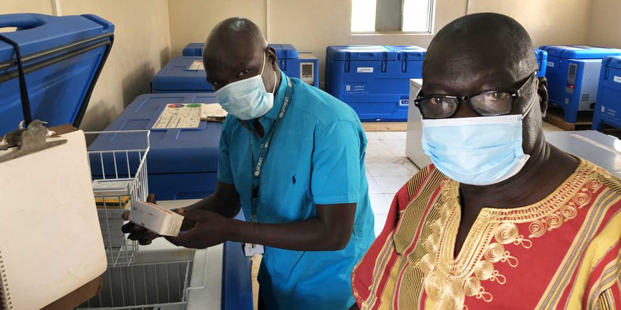 @ UNICEFSouthSudan/Willemot Evans Ariko Shawish (right) Manager, Expanded Programme for Immunization, Ministry of Health, Western Equatoria State and Daniel Drinchi, Health Officer, UNICEF Yambio field office, inspecting the central cold chain storage in the state capital Yambio. The cold chain is now used for measles and polio vaccines among others and will soon also be used for COVID-19 vaccines.