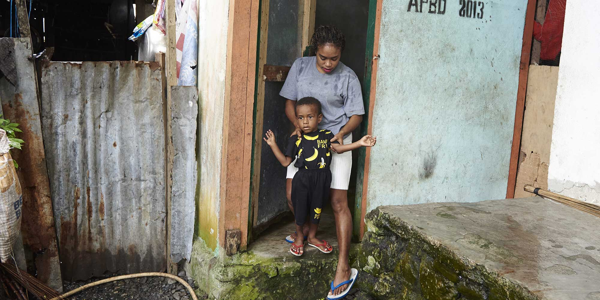 Aumelina helps her child in using the family latrine outside their home in Tablanusu, a 100 per cent Open Defecation Free (ODF) village in Papua Province, Indonesia. – Photo: UNICEF/UN0248720/Noorani