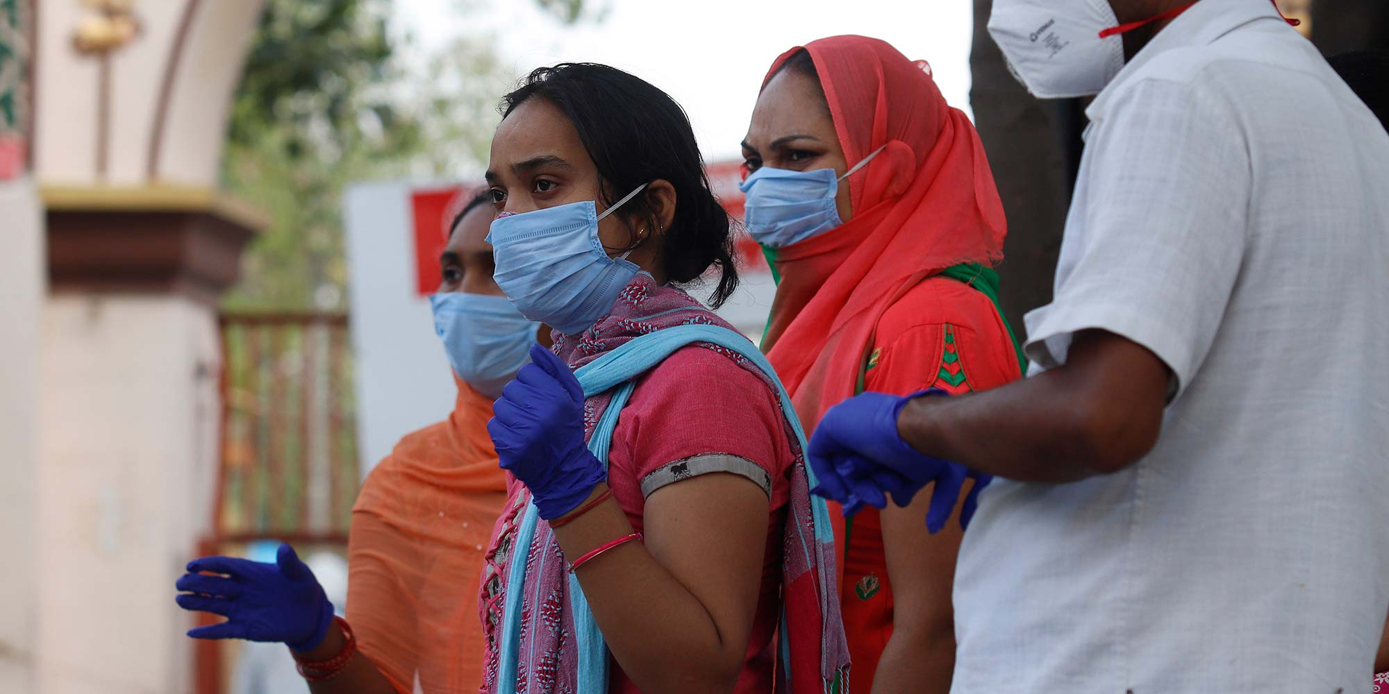 Indian health workers wearing personal protective equipment (PPE) and relatives carrying the mortal remains of a COVID-19 victim at the cremation ground.
