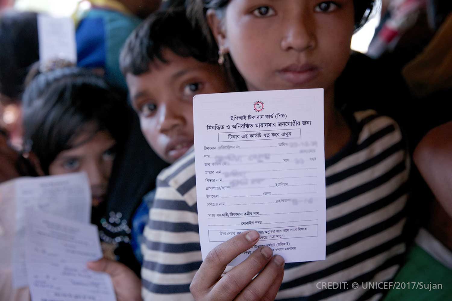 A girl holds up vaccination card